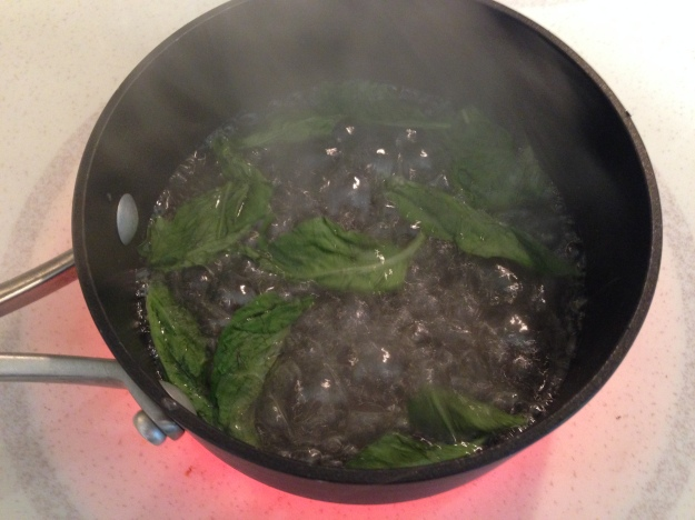Basil infusing into the simple syrup before being taken off the stove.